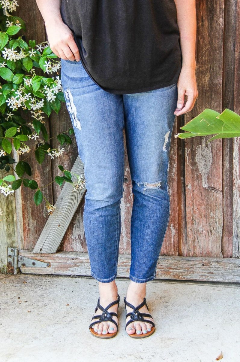 woman in blue jeans with black tank and black sandals