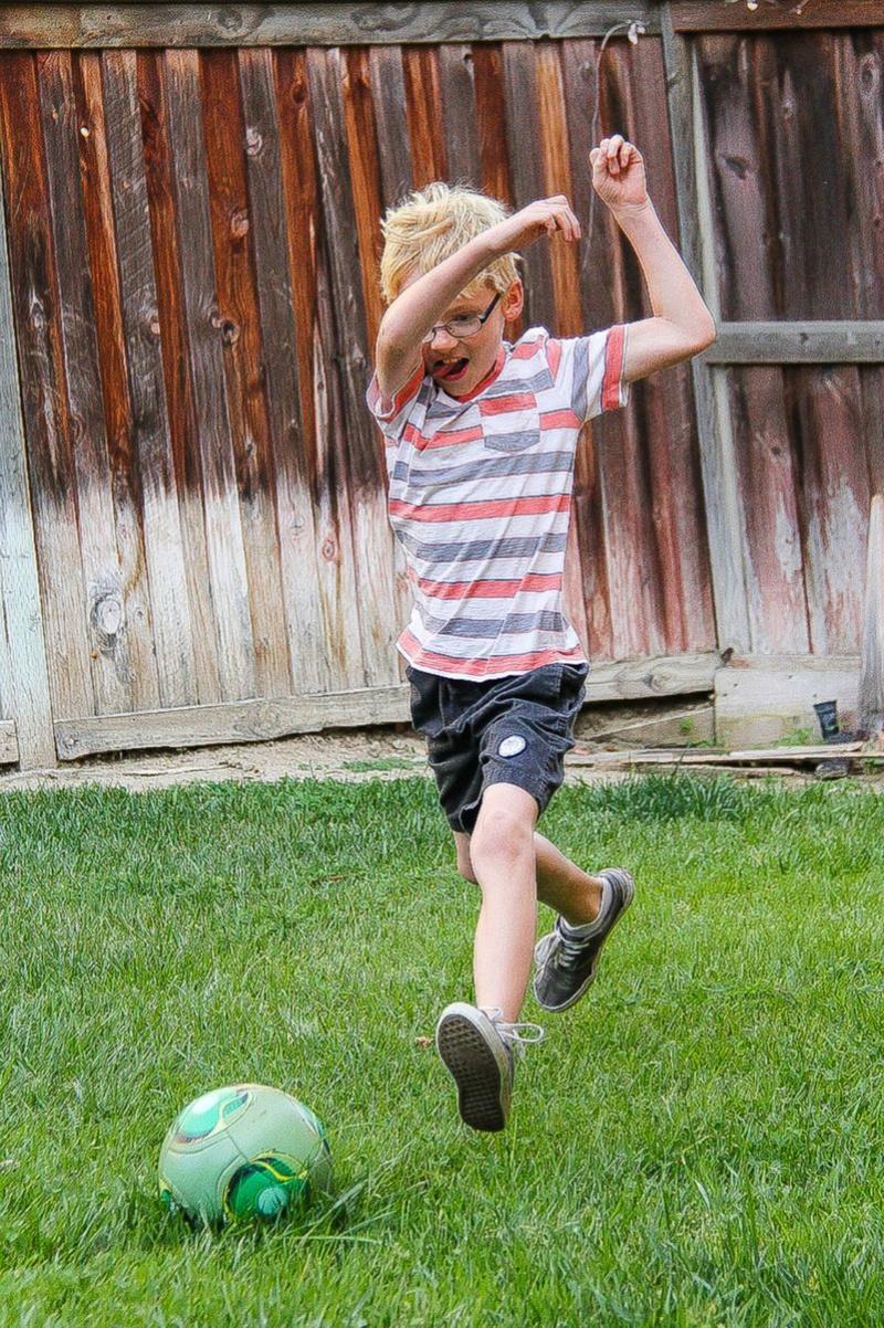 a boy kicking a soccer ball in the backyard