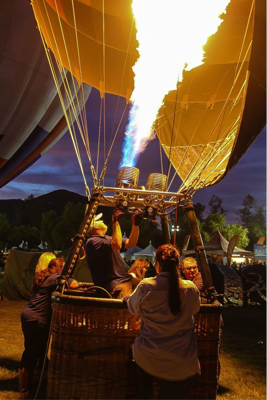 people inside a hot air balloon basket after dark