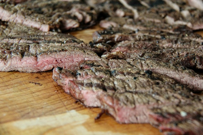 grilled steak cut into thin slices on a cutting board