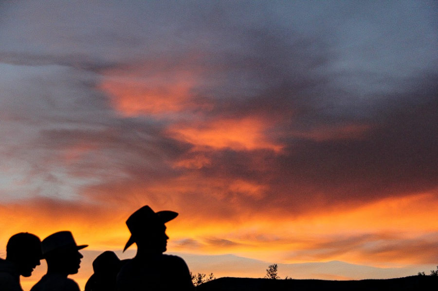 silhouettes of men in various hats with the sunset in the background