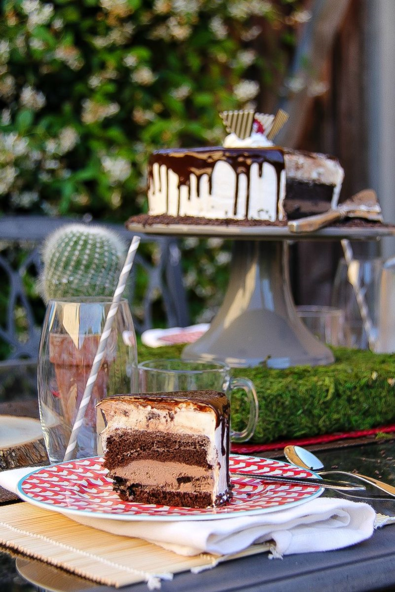 a slice of ice cream cake on a red and white plate with the cake stand in the background