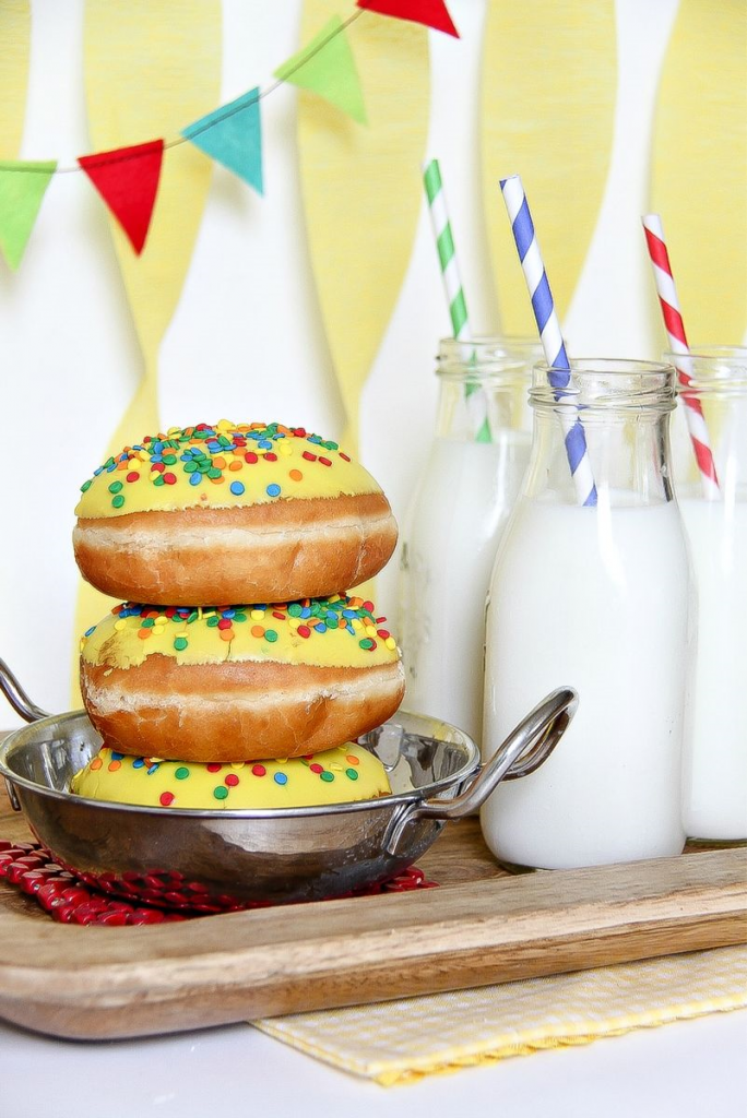 donuts on a silver dish with milk bottles and straws in front of a birthday banner
