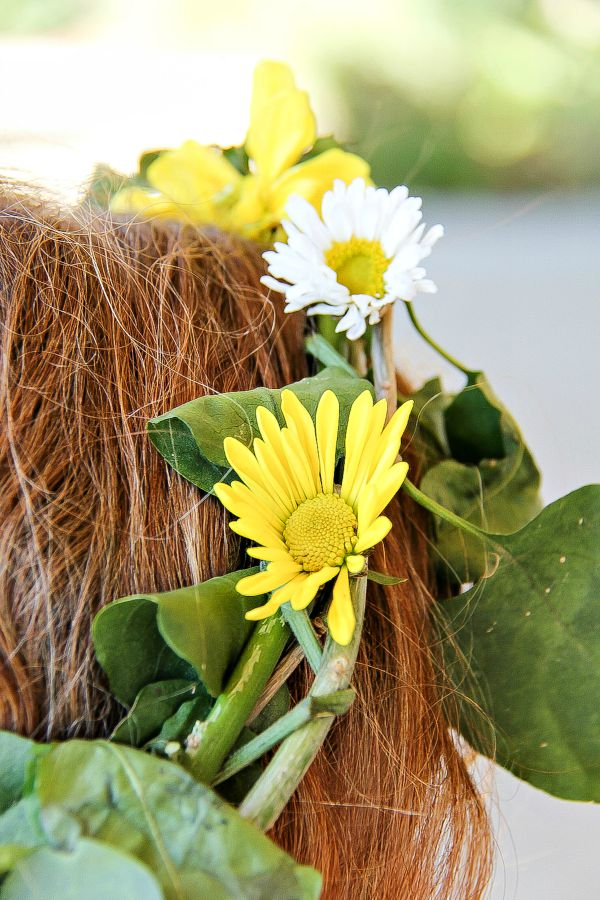 a yellow and white fresh flower crown on a girls head