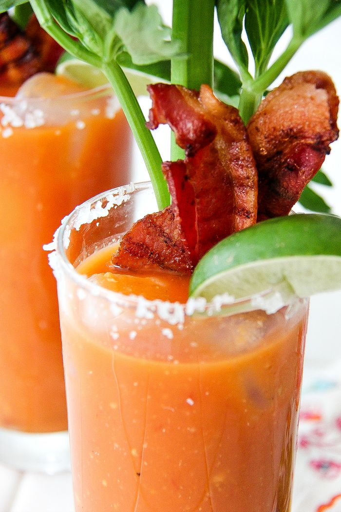 up close shot of a glass rimmed with sugar and filled with a bloody mary, bacon, lime, and celery