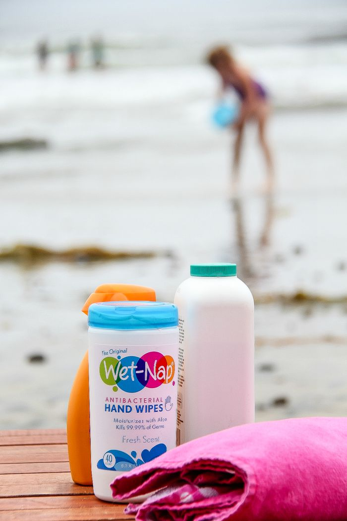 Wet Nap antibacterial wipes, with a towel, and sunscreen and kids at the beach