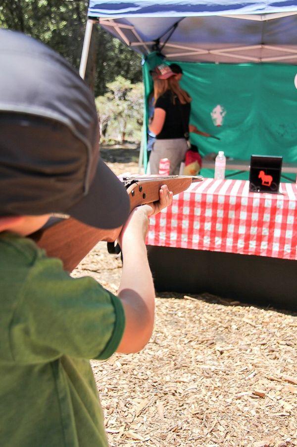 boy shooting a wood elastic band gun at a target