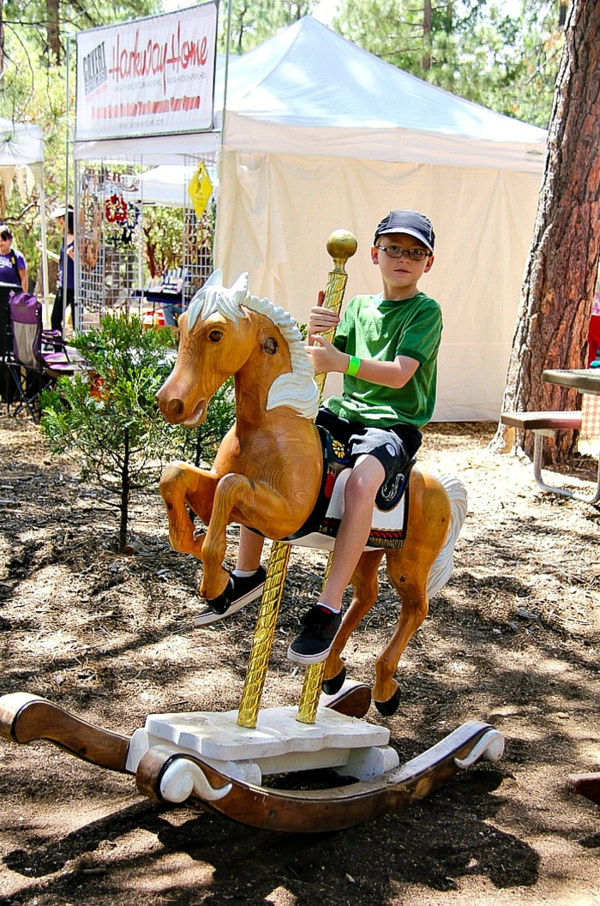 boy riding a hobby horse outdoors