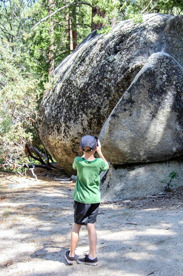 boy taking a photo of a boulder