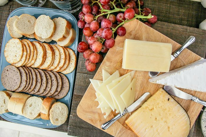 cheese board and crackers with red grapes