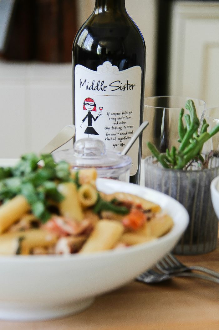 a bowl of pasta with a bottle of Middle Sister red wine