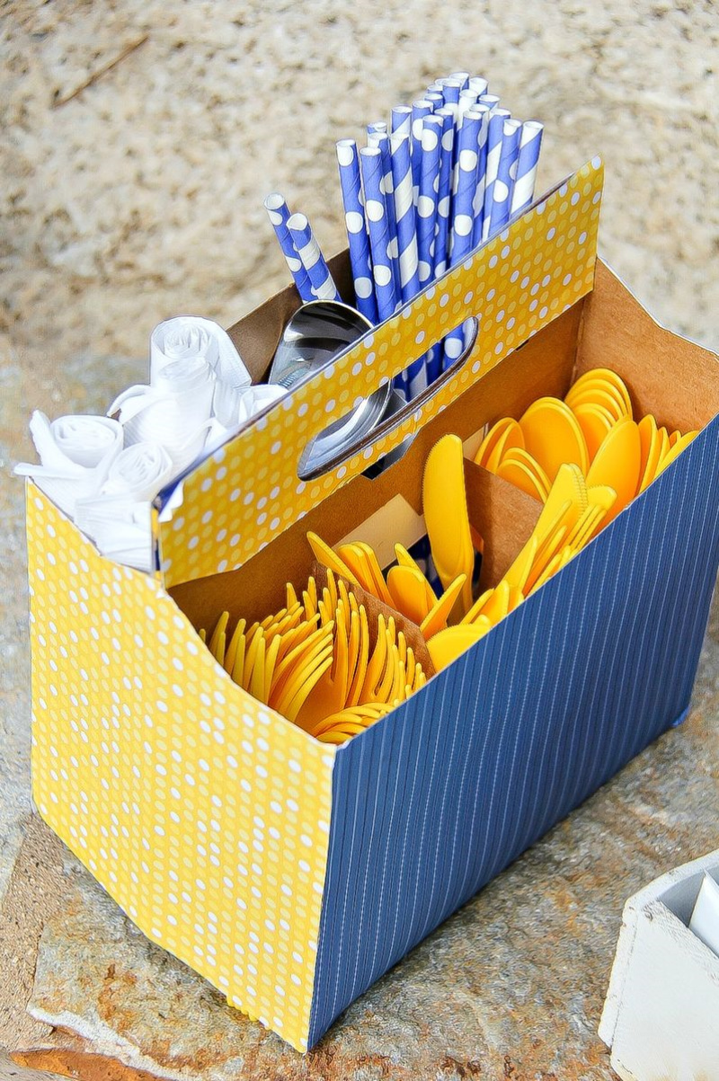 a yellow and blue utensil caddy filled with napkins, straws, and utensils