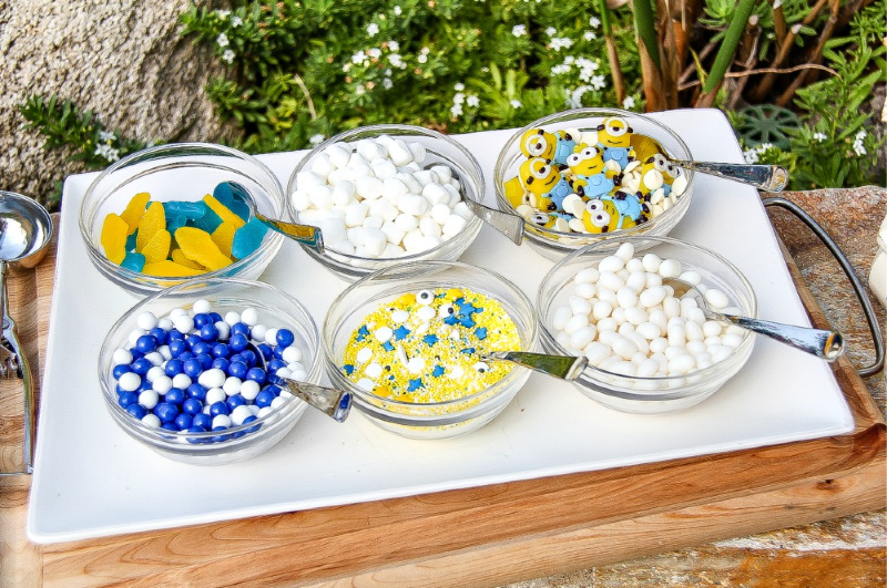 blue, yellow, and white ice cream toppings in glass bowls