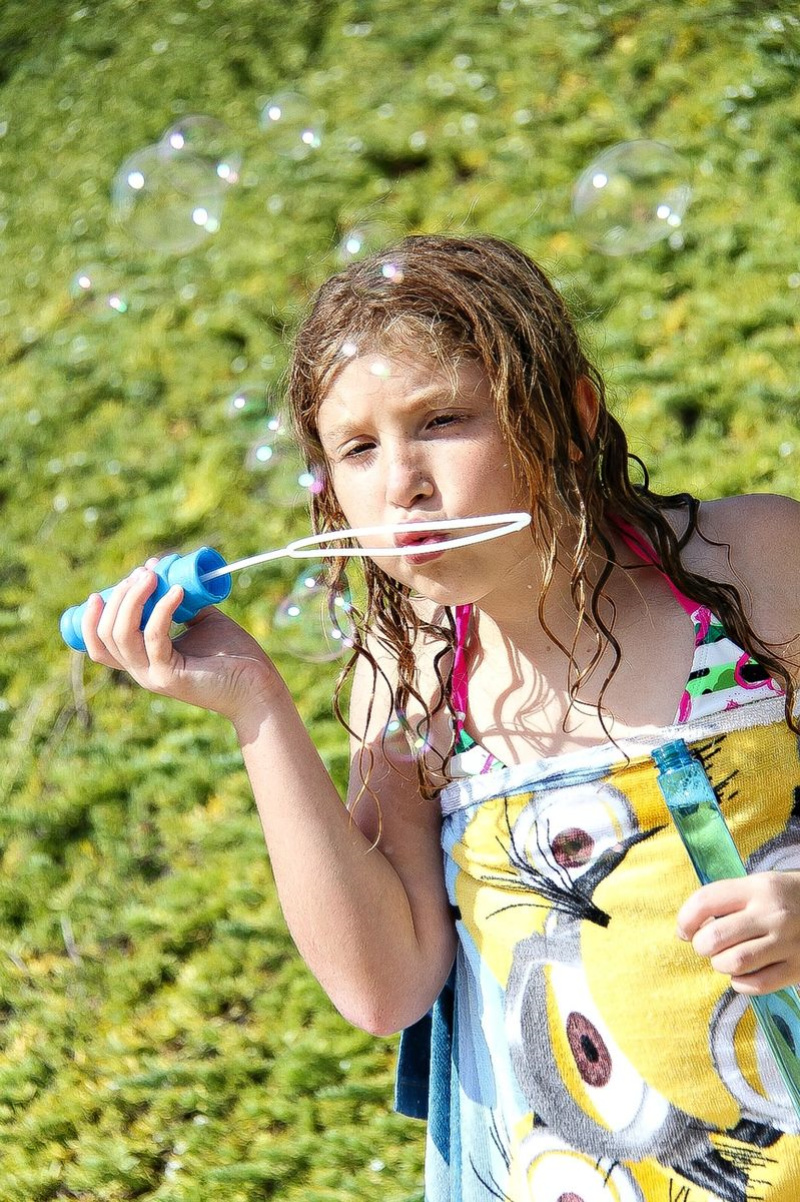 a girl using a bubble wand to blow bubbles