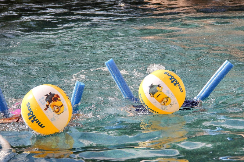 kids in a swimming pool playing with minion beach balls and noodles