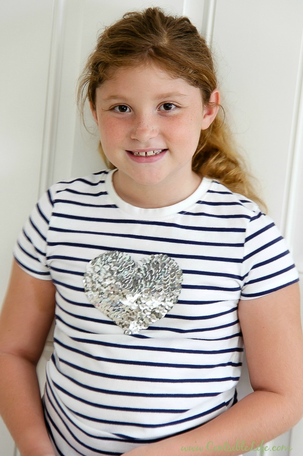 girl wearing a black and white stripe tee with a silver sequin heart on it