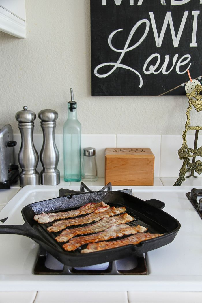 a cast iron grill pan on the stove with bacon cooking