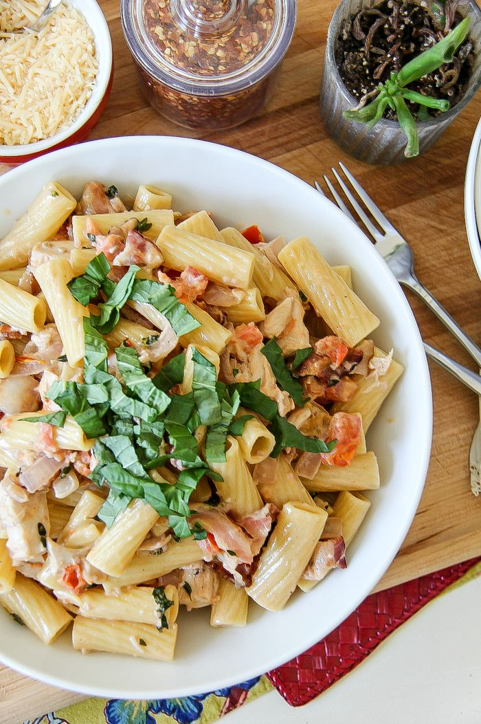 rigatoni pasta with chicken and bacon surrounded by red pepper flakes, grated cheese, and fresh herbs