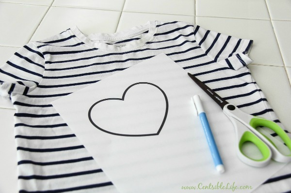 a girls black and white tee with a heart template, pen, and scissors