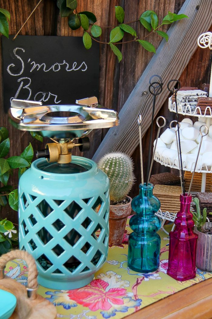 a portable camp stove in a candle holder with colorful jars filled with metal skewers for s'mores