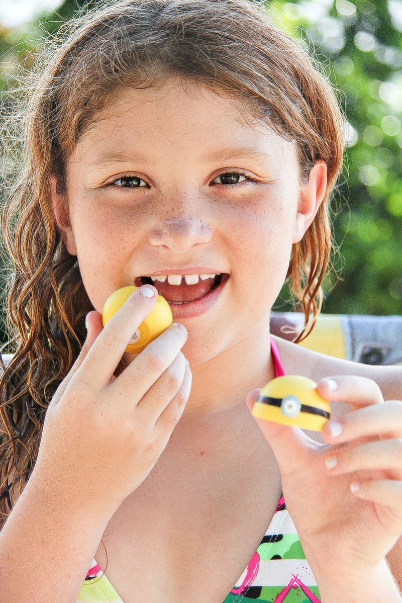 a girl using EOS yellow lip balm with a minion face drawn on it