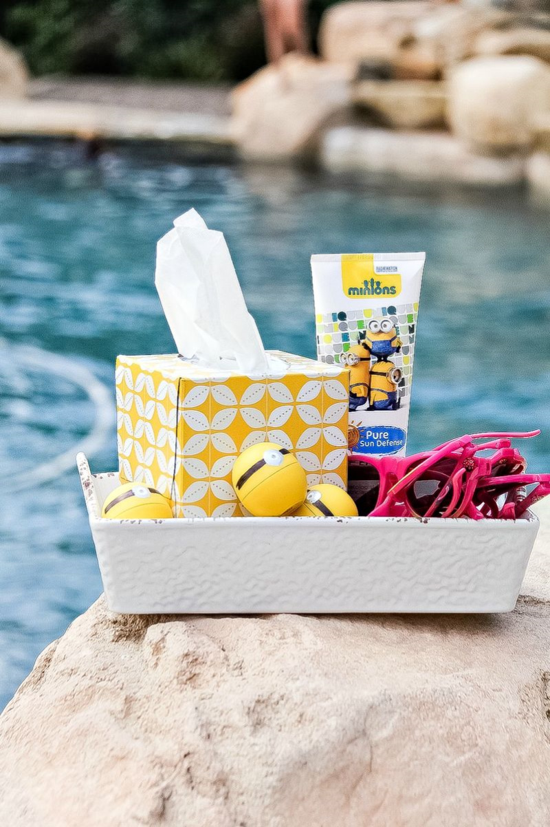 A box filled with minions sunscreen, lip balm, and sunglasses in front of a swimming pool
