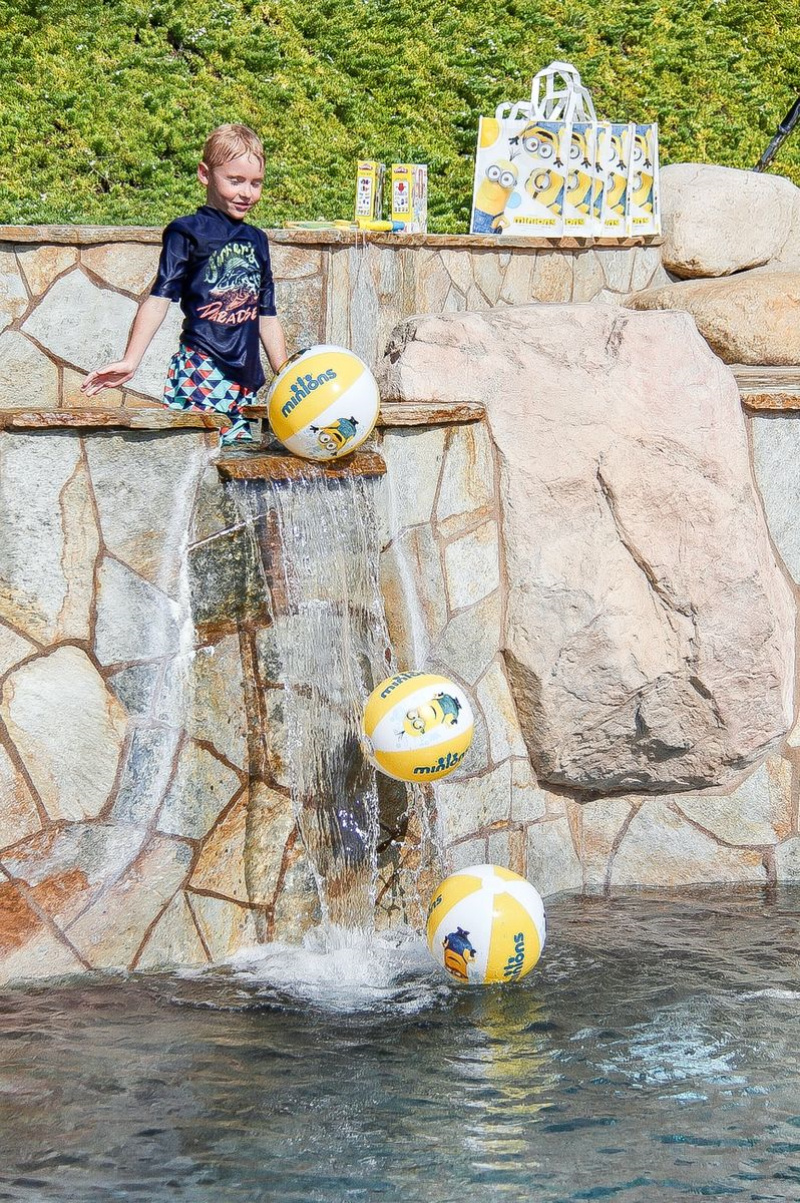 a boy putting minion beach balls over a waterfall