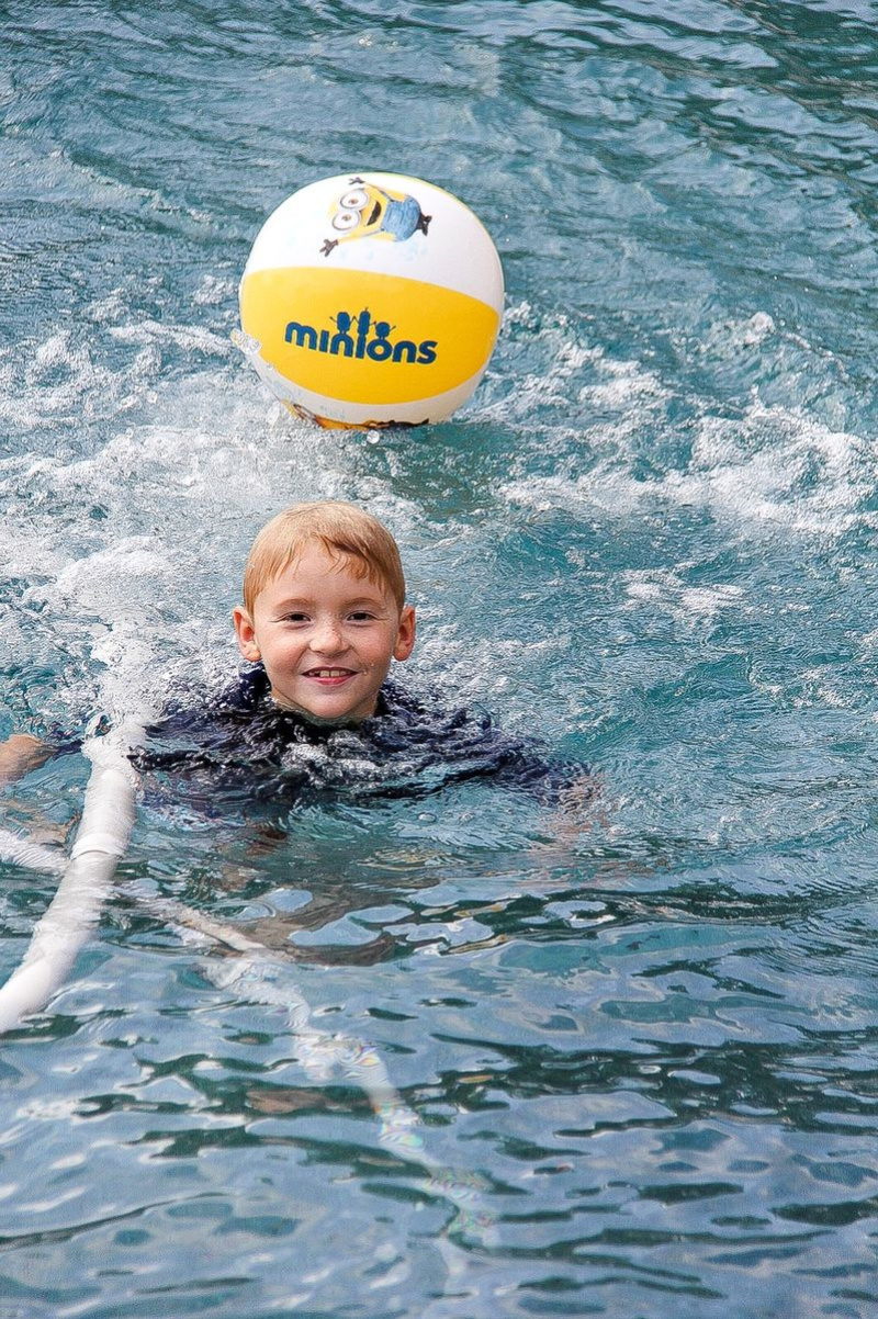 a boy playing in a swimming pool with a minions beach ball