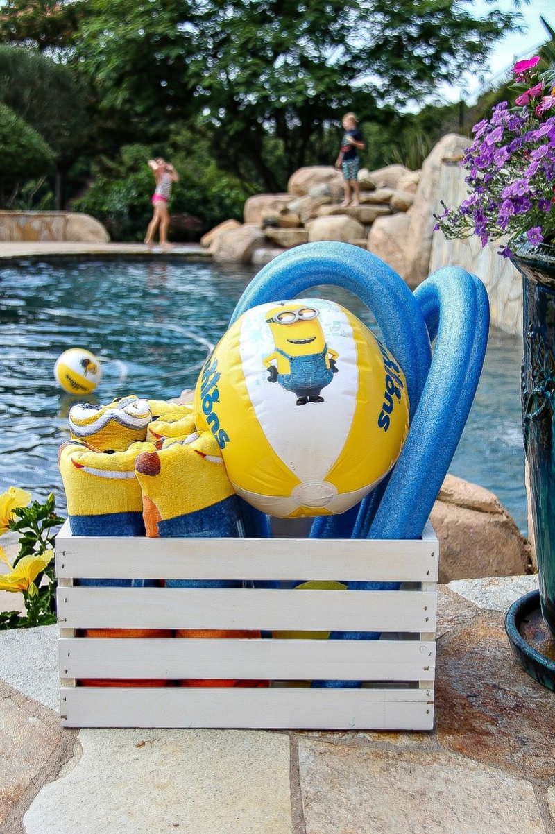 a white box filled with minion towels and pool tools with a pool in the background