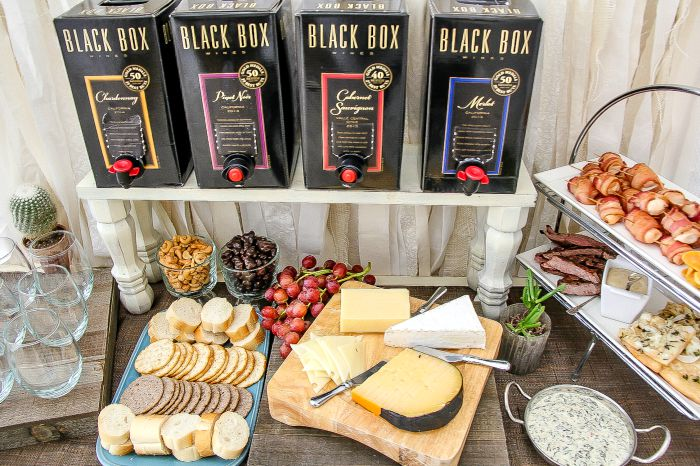 black box wines on a table with assorted cheese, craackers, fruit, and appetizers