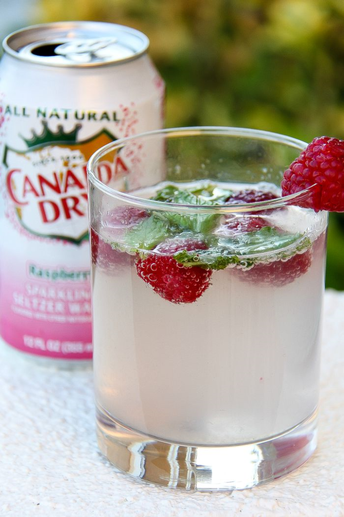 canada dry sparkling raspberry with a cocktail in a glass garnished with fresh raspberries