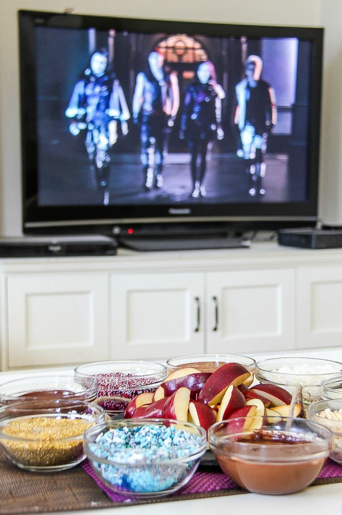 disney descendants playing on a television with apple slice movie night treats
