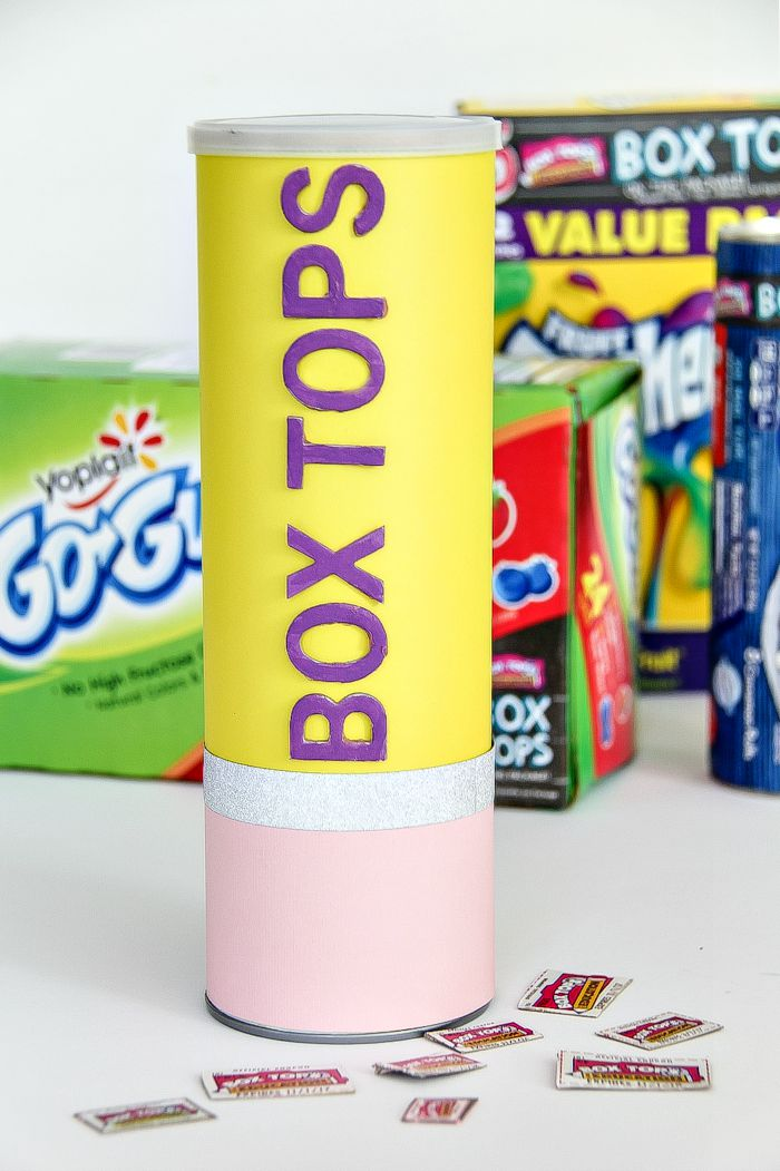 a box tops collection canister shaped like a pencil with products in the background that have box tops