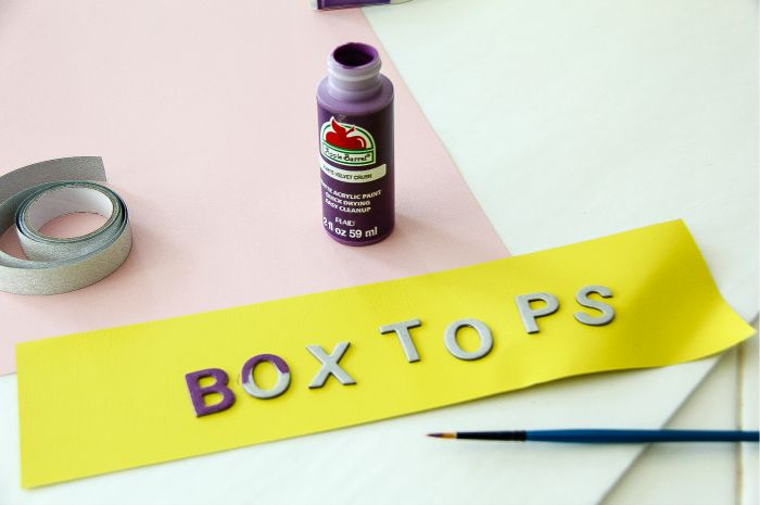 cardboard letters spelling box tops being painted
