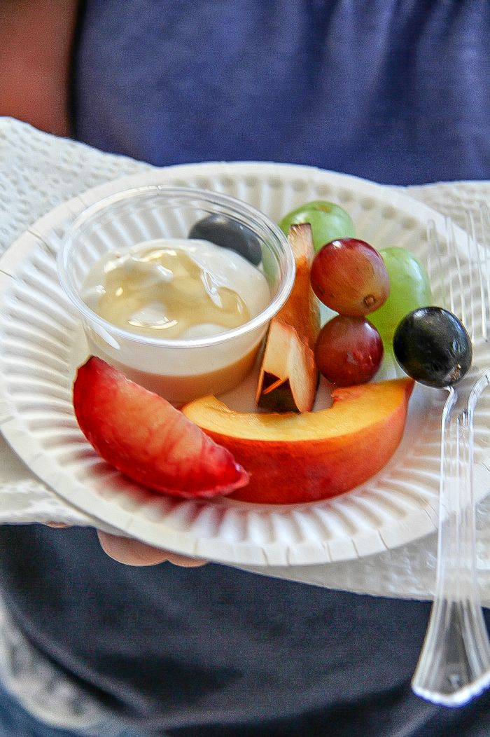 girl holding a paper plate with fresh fruit and yogurt dipping sauce in a container