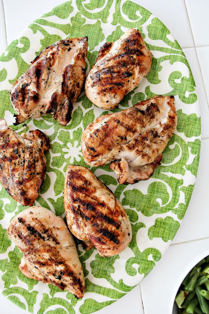 grilled lemon chicken breasts on a green and white serving tray