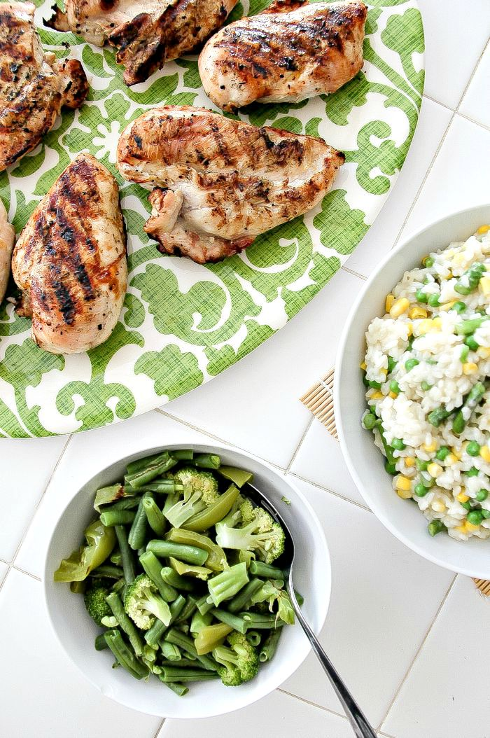 grilled chicken on a serving plate with risotto and steamed green vegetables