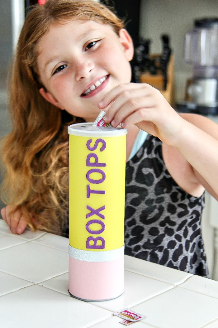 a girl putting box tops into a pencil box tops collection container