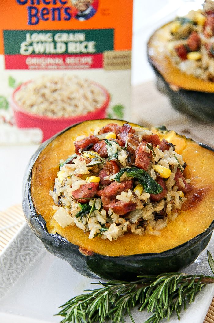acorn squash stuffed with sausage and rice with a box of uncle bens wild rice