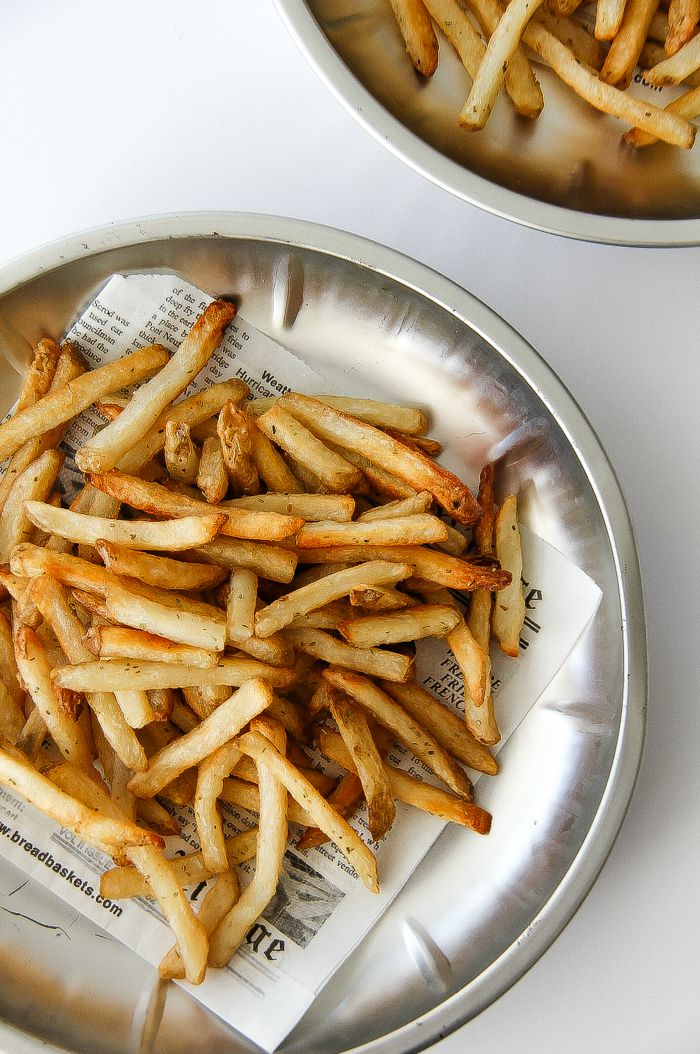 french fries on a silver tray with newspaper print parchment paper