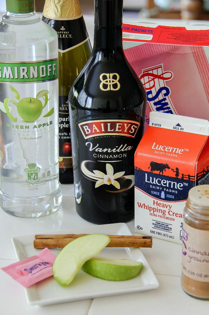 Baileys, apple vodka, cream, and cinnamon stick to make a cocktail