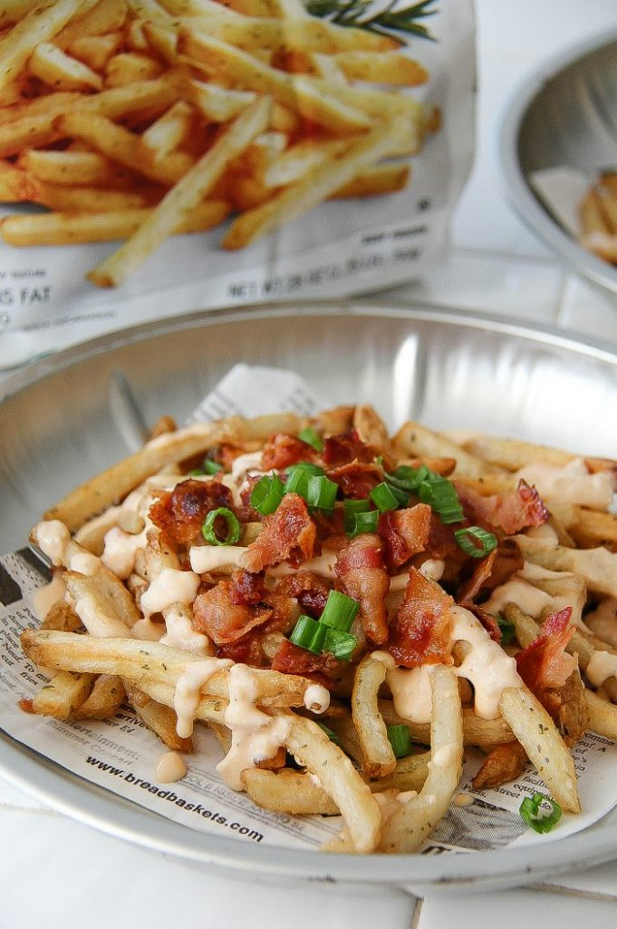 french fries topped with bacon, sauce, and green onions