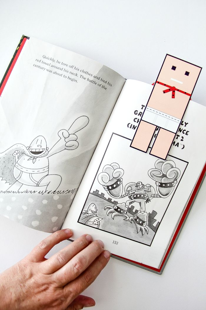 hand holding open a captain underpants book with a paper bookmark