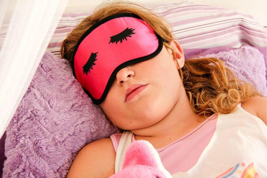 girl sleeping wearing a pink eye mask