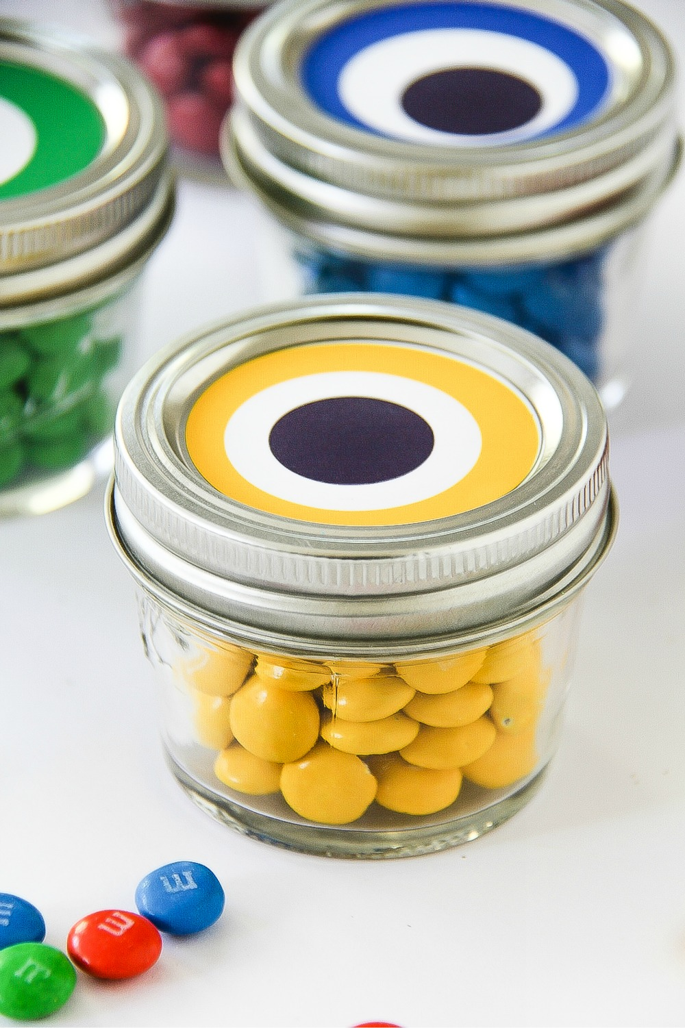 small canning jars with colorful candy and eyeballs on top to look like monsters