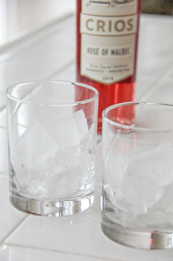 ice cubes in glasses with rose malbec bottle in the background