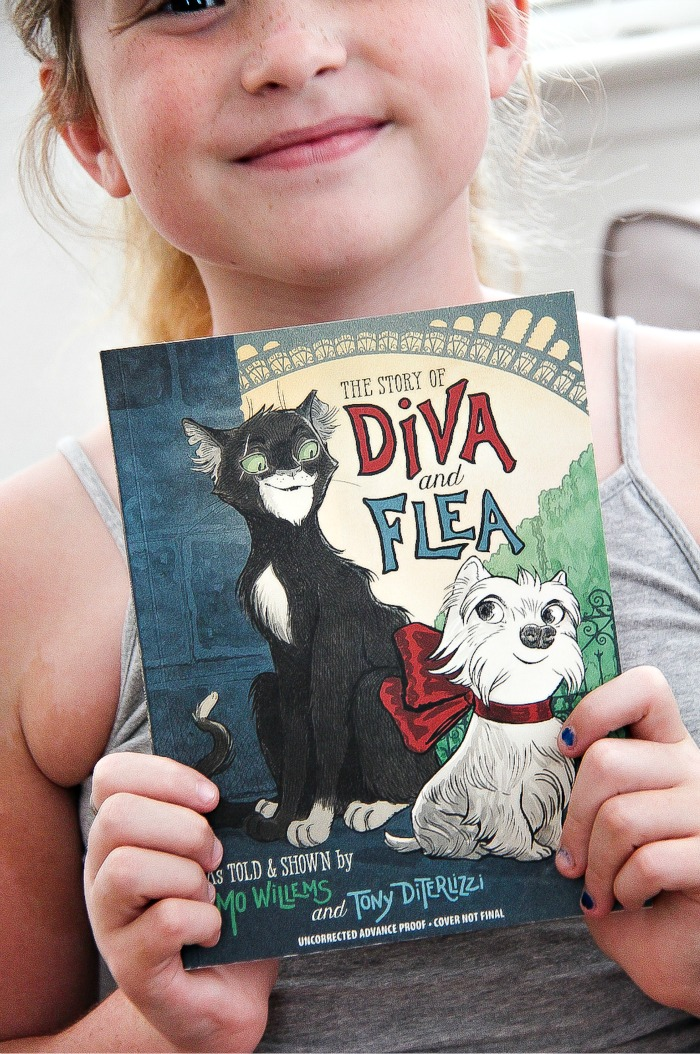 girl holding the book Diva and the Flea