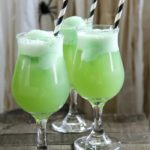 green drinks in cocktail glasses with a spider for halloween