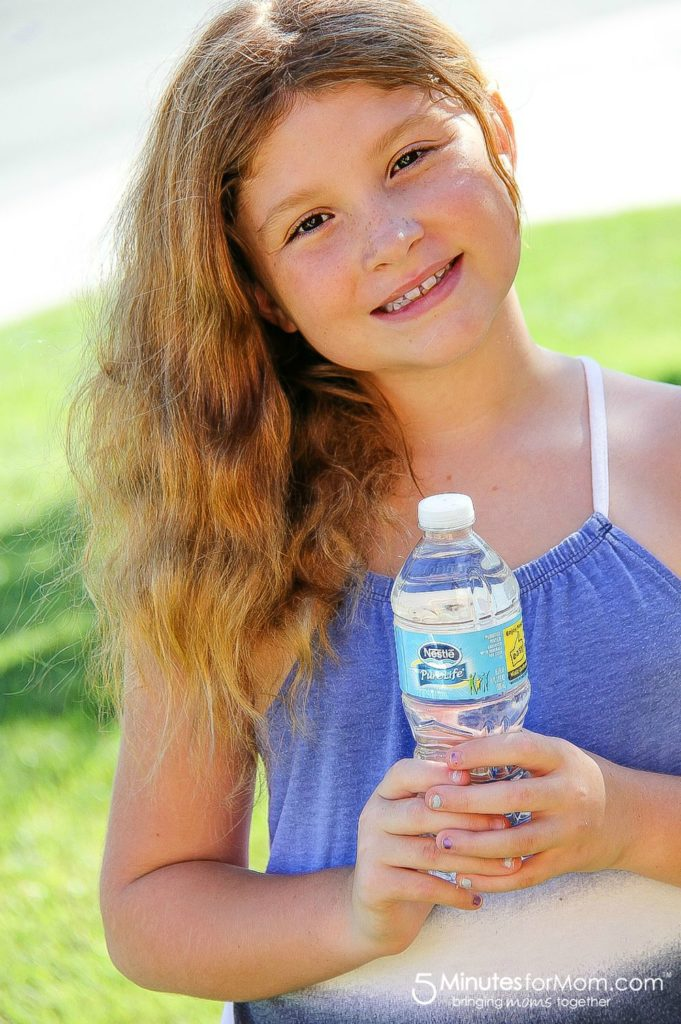 girl holding a nestle pure life water bottle
