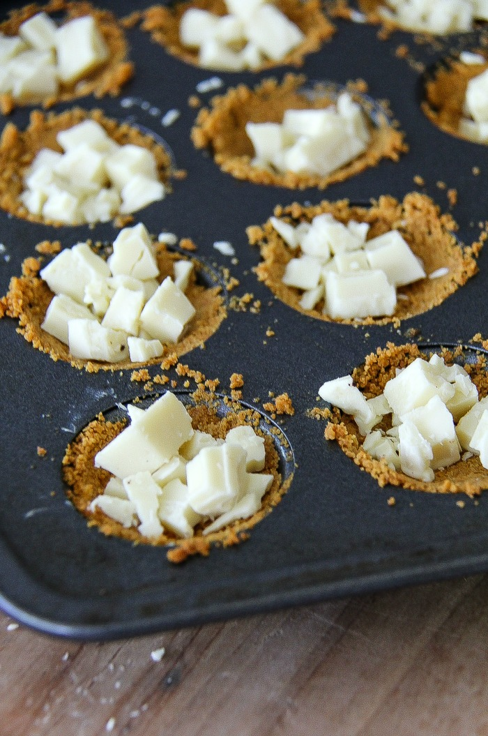 white chocolate in graham cracker cups in a baking pan